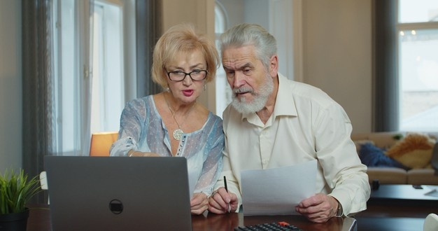 Mature couple looking at bills at home in front of a computer.